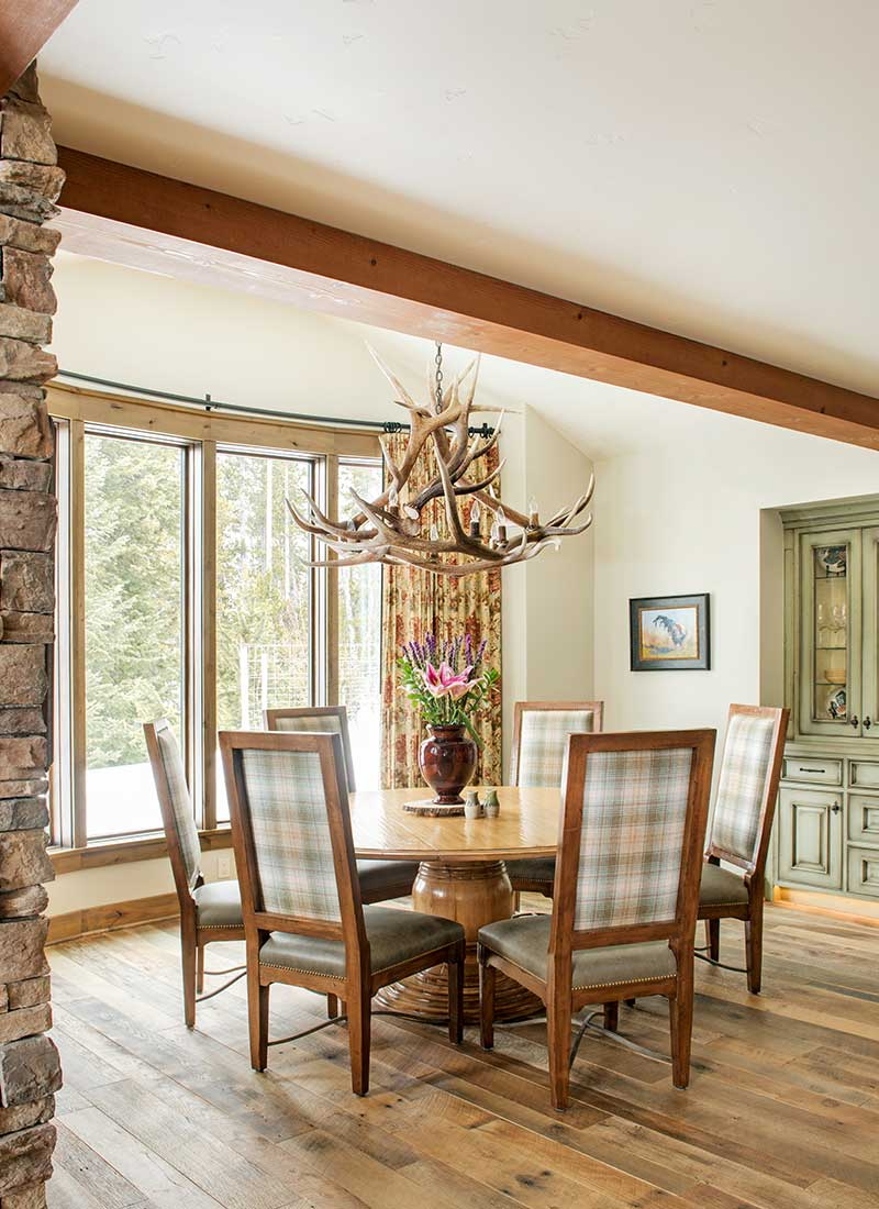 dining room with antler chandelier and plaid chairs of Moonlight residence designed by Elizabeth Robb Interiors
