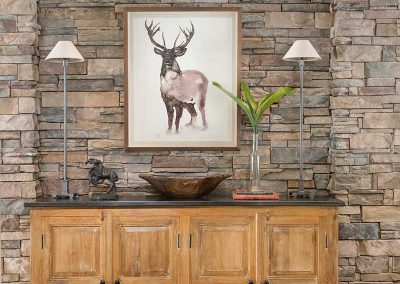rock wall with dining room sideboard of Moonlight residence designed by Elizabeth Robb Interiors