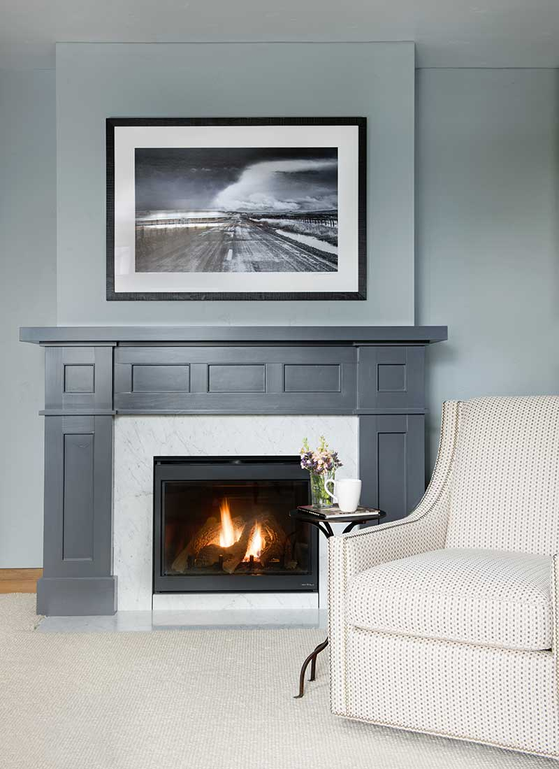 gray wall and fireplace with a white chair of Moonlight residence designed by Elizabeth Robb Interiors